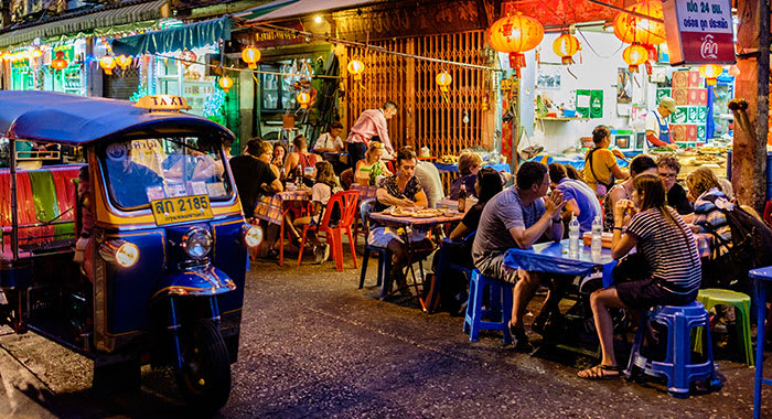 people sat outside eating and drinking on Thai streets