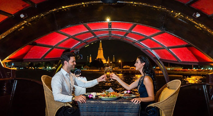 Couple dining aboard the river cruise in Thailand