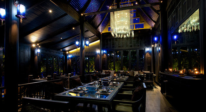 Inside the Black Ginger restaurant with dark lighting and dark wood tables