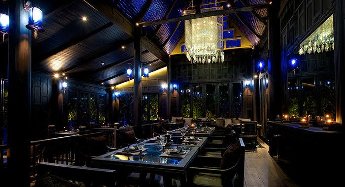 Inside the Black Ginger restaurant with dark lighting and dark wood tables