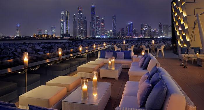 Outdoor terrace at night overlooking sea and Dubai city skyline
