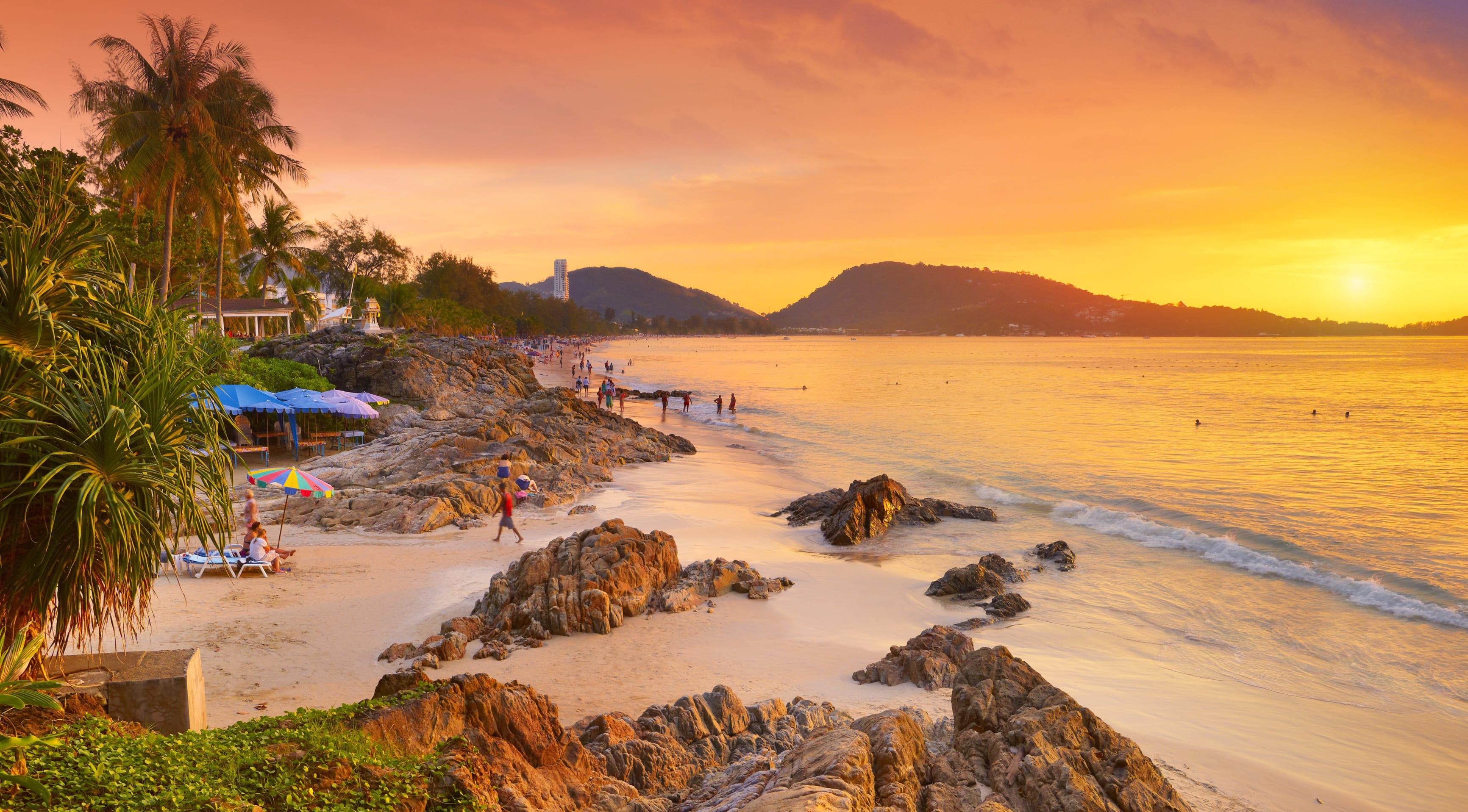 Patong beach, sea and mountains as the sun sets a golden orange colour