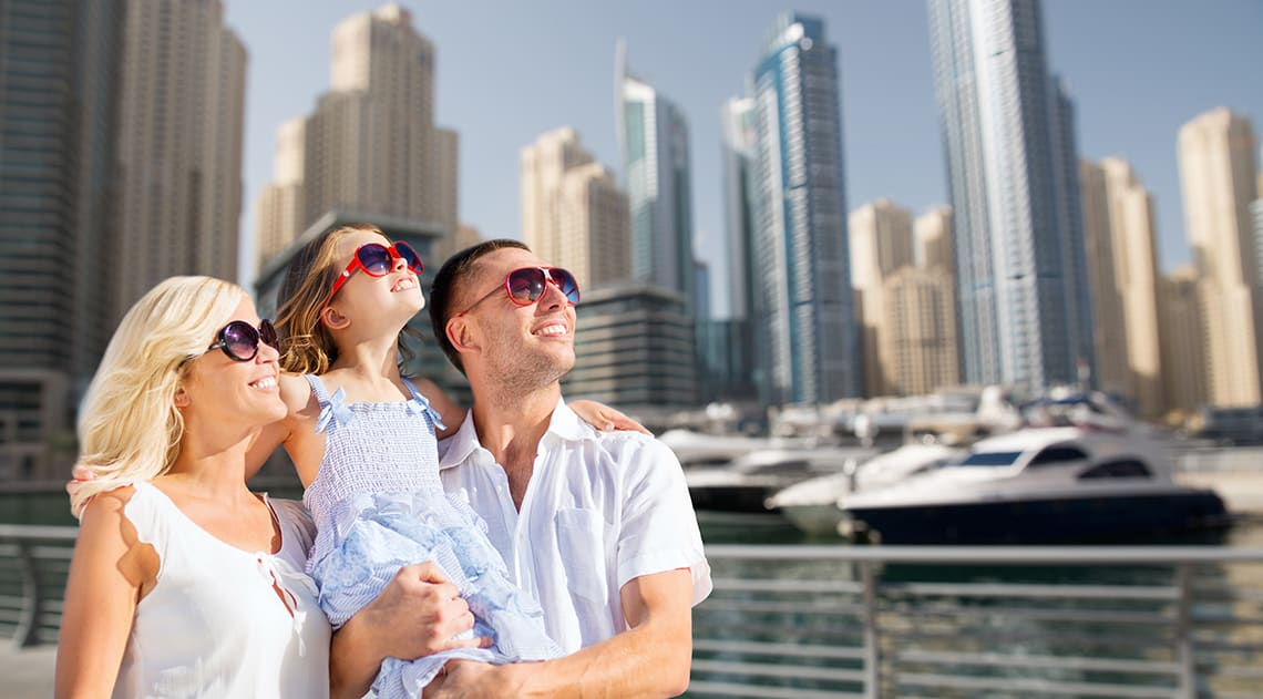 Family of three with sunglasses looking at attractions with the city behind them