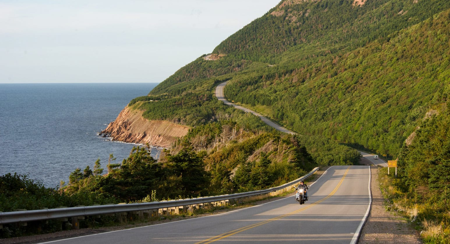 A motorbike racing round an island road with hills and sea in the background