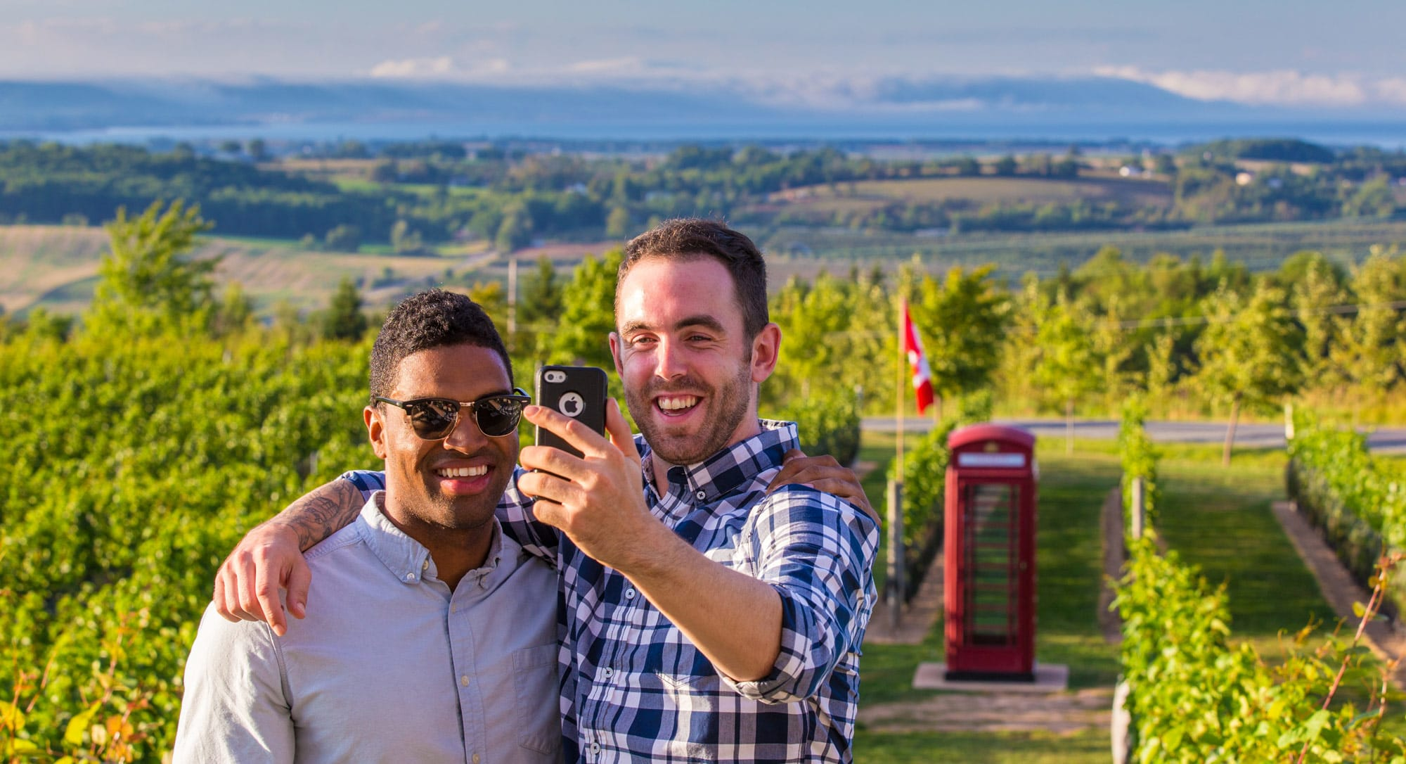 Two men taking a selfie in front of the vineyard and a wine shop