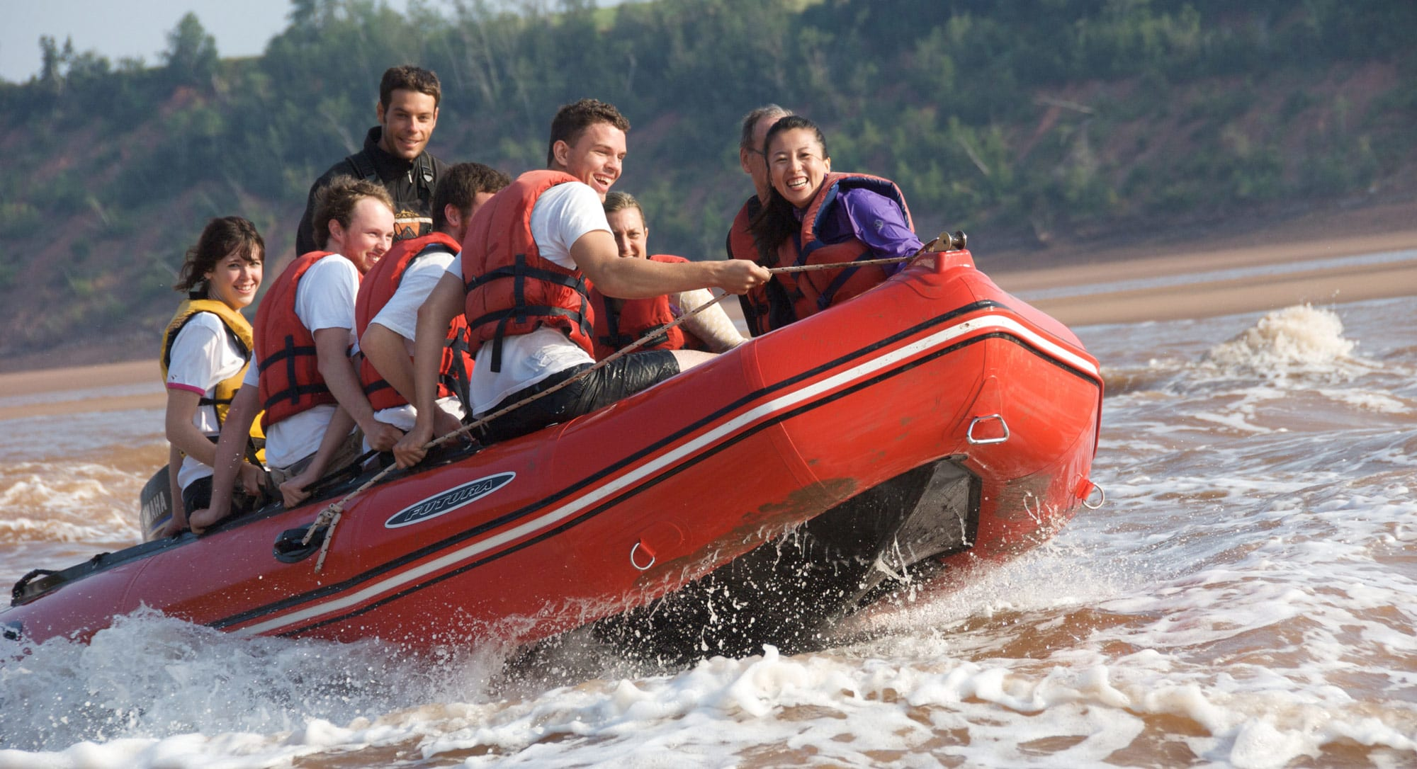 A group of young people tidal bore rafting and mudsliding