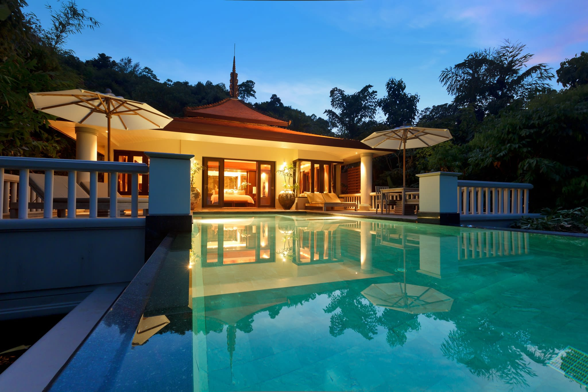 Villa with outdoor decking and swimming pool surrounded by trees