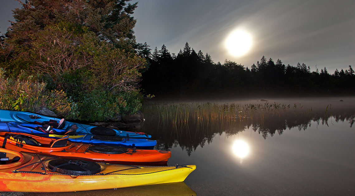 The moon reflecting off tge dark water with kayaks on the shore and foliage next to the water