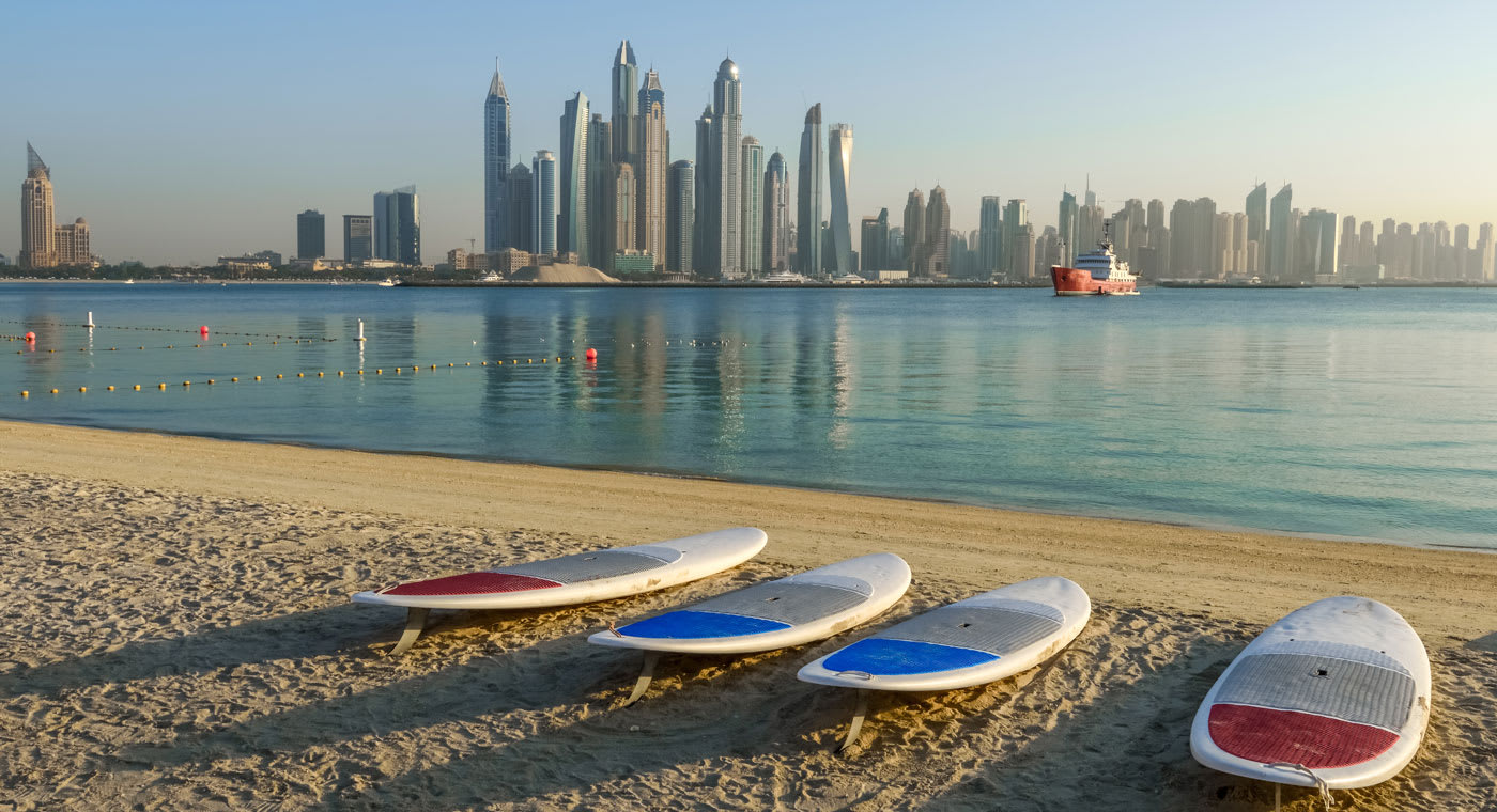 Dubai beach with still blue water, the Dubai skyline in the background and 4 white surf boards on the sand