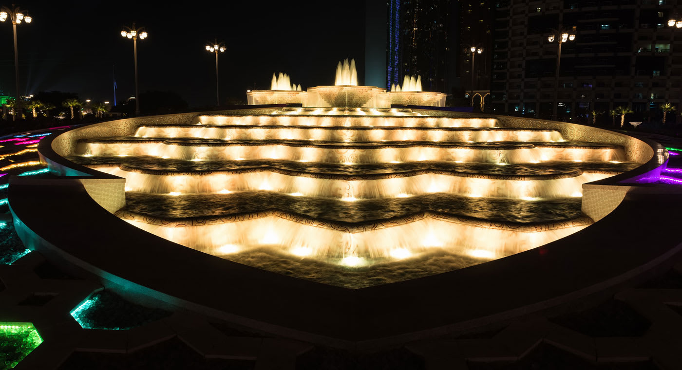 A fountain at night lit up in multi colours in Abu Dhabi