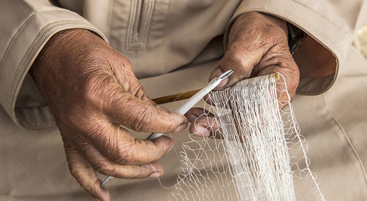 A close up of an old persons hands making a net