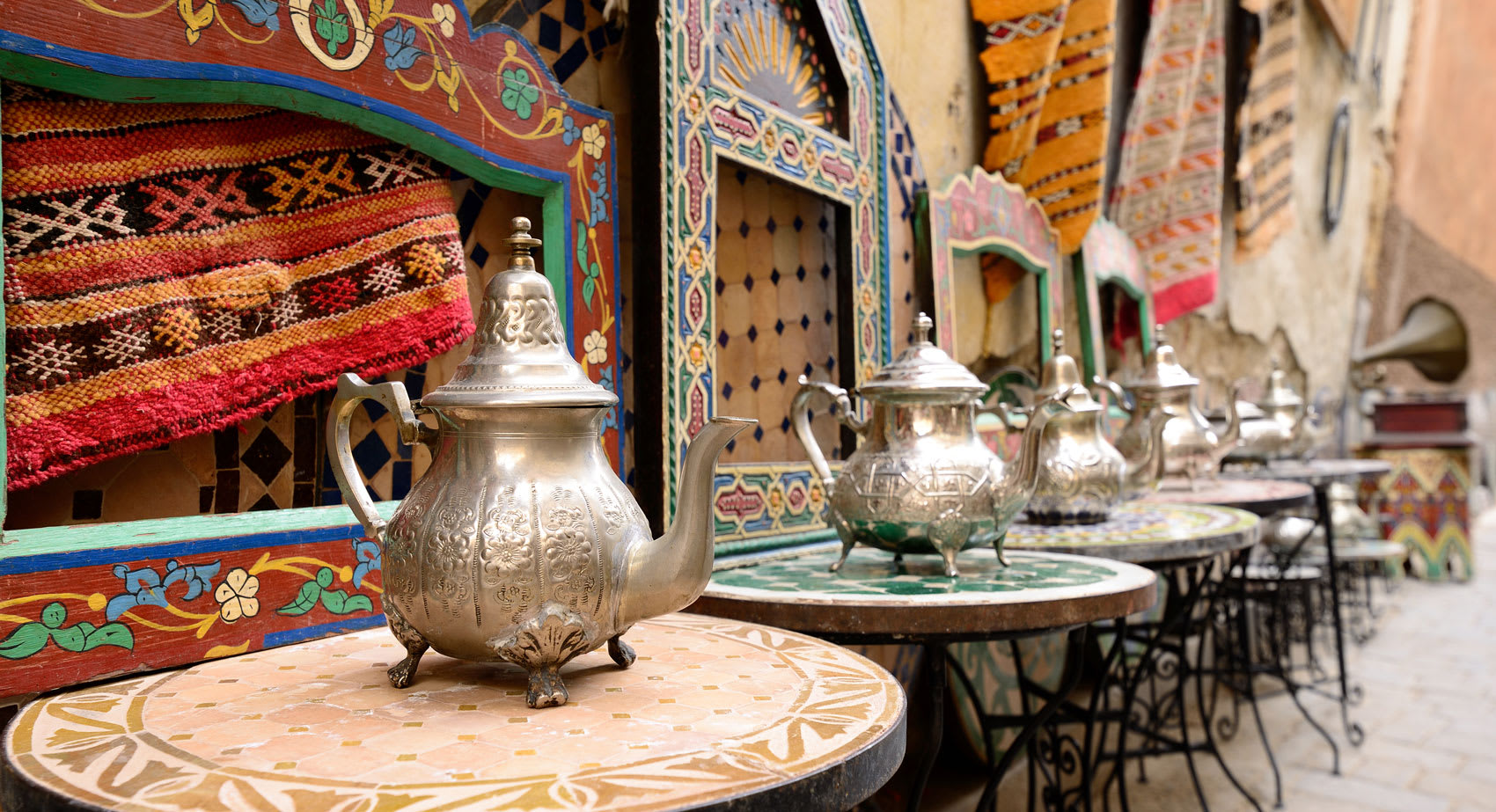 Marrakesh Market with pained coloured tables each with a large golden teapot on it