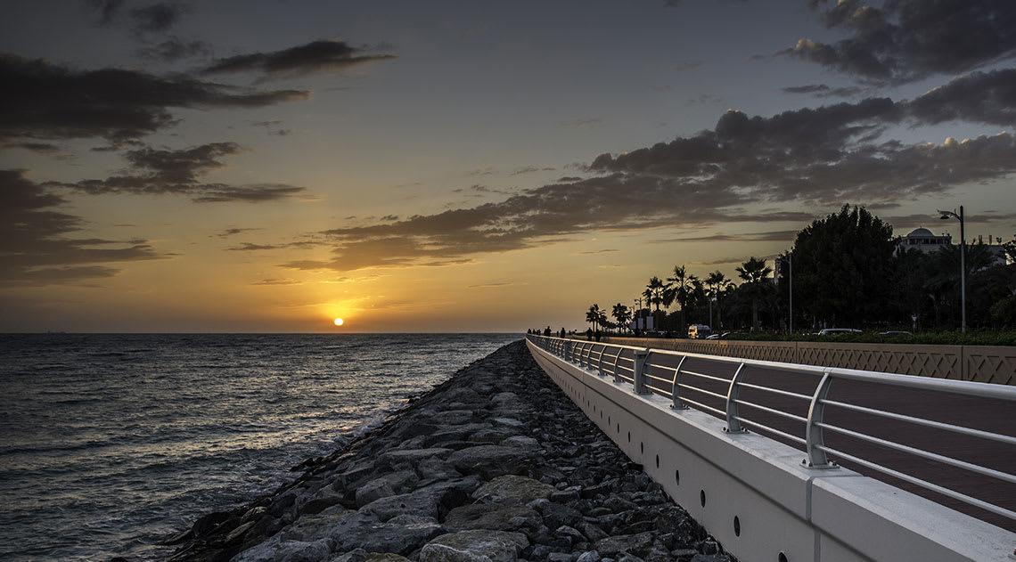 The sea, rocky coastline and boardwalk as the sun sets