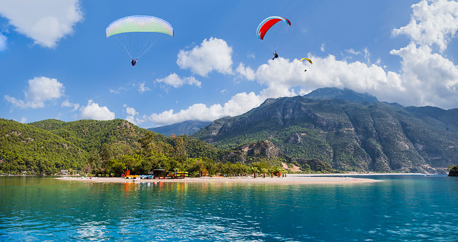 Paragliding by the beach surrounded my green mountains