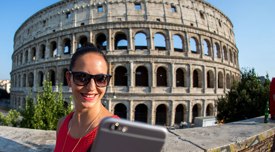 A women taking a selfie in front of the coliseum