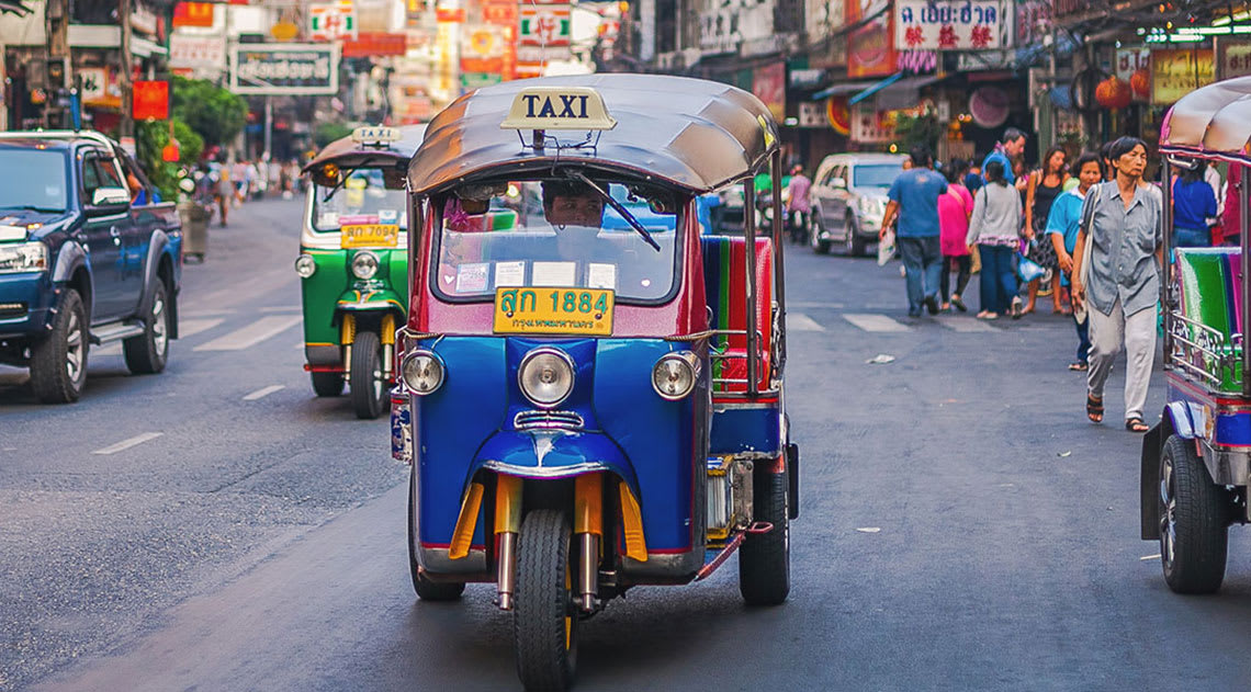 A busy Bangkok street with colourful tuk tuks and pedestrians