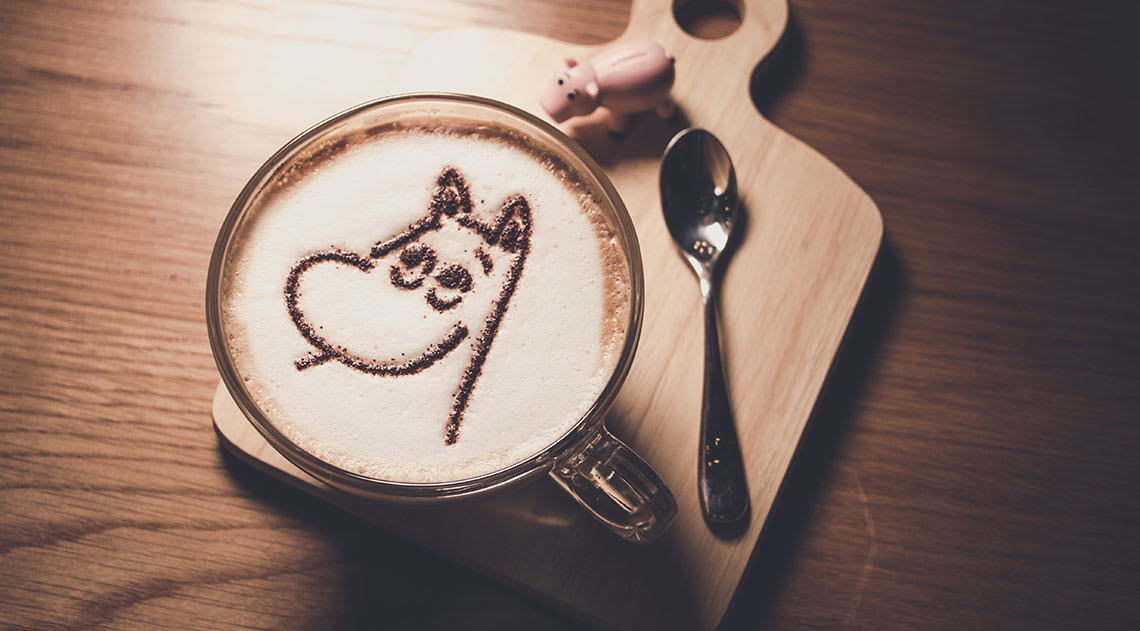 An aerial view of a coffee with a moomin picture made of chocolate