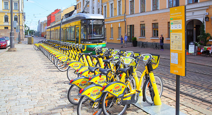 A line of yellow bikes that can be rented and a tram