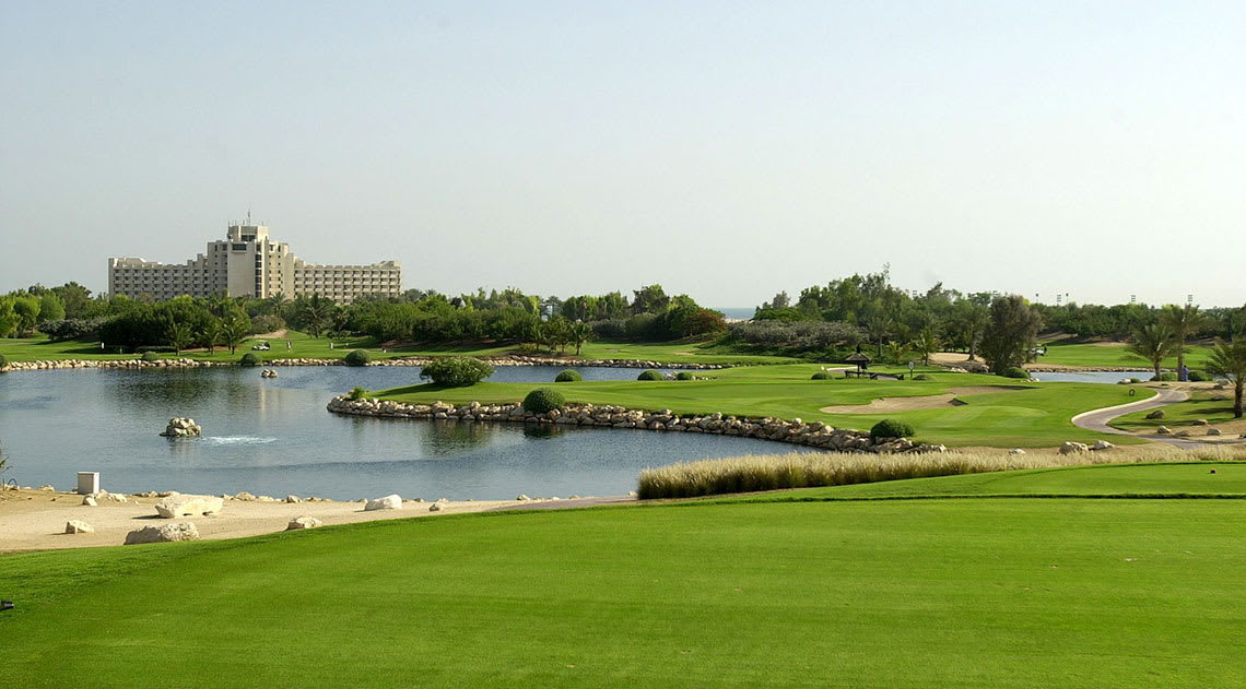 Golf course, lakes and palm trees with hotel in background