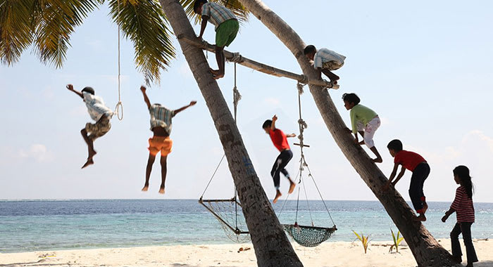 Children playing on a climbing frame on the beach