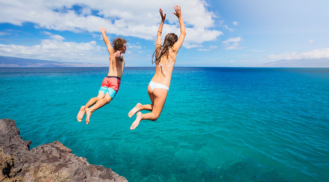 A boy and girl in swimwear jumping off a cliff into the blue water