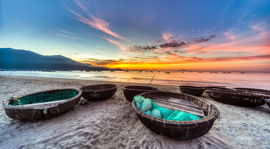 Sunset on the beach with straw boats on the sand