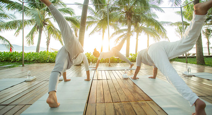 People wearing white doing yoga outdoors