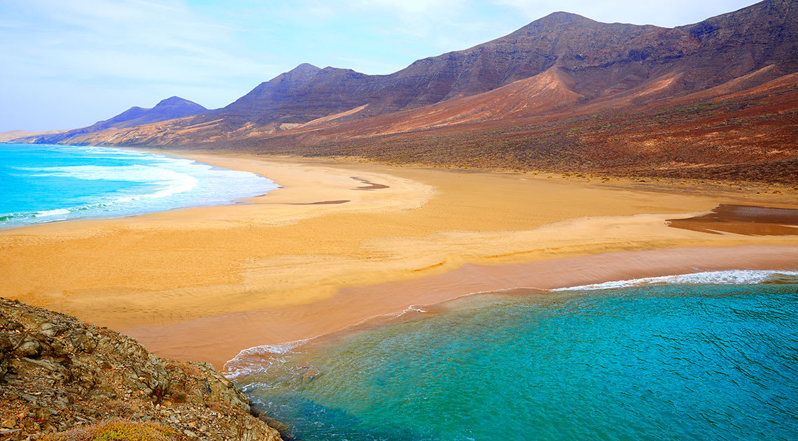 The beach in Fuerteventura with golden and and turquoise water