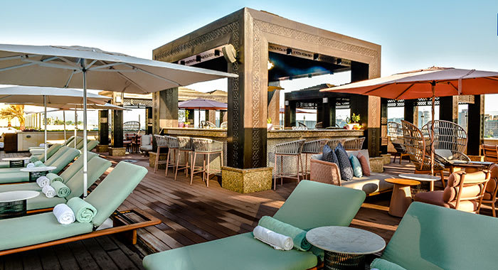 Wooden sundeck and bar with sunbeds, tables and parasols