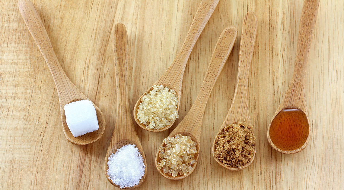 Differnt types of sugar on wooden spoons