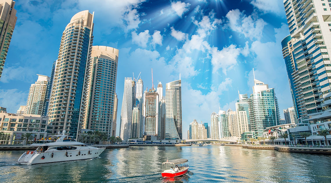 Abu Dhabi skyline by sea with boats
