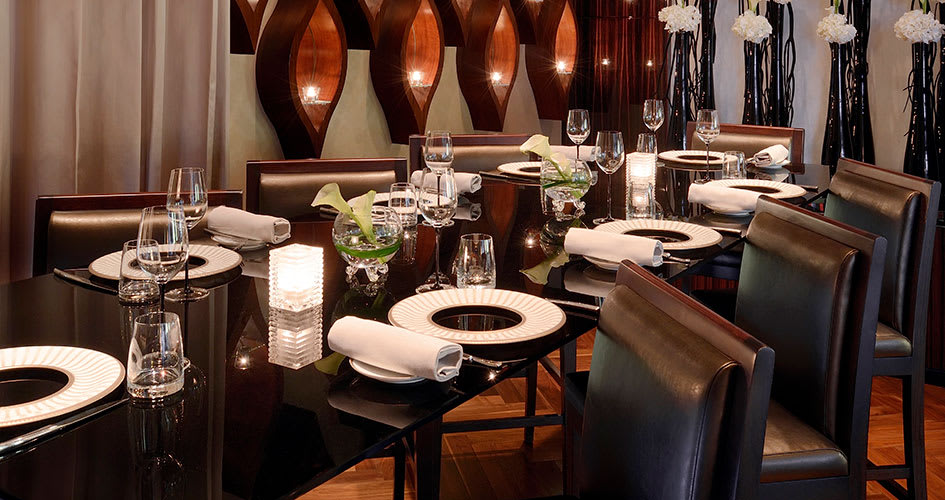 Restaurant with dark furnishings, flowers and candles