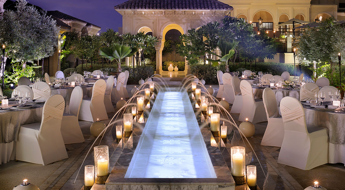 Long waterfreature at night with candles and wedding style seating