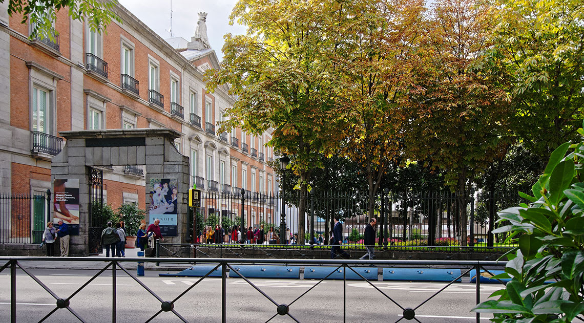 Thyssen-Bornemisza museum building with people going into the entrance and trees and a road