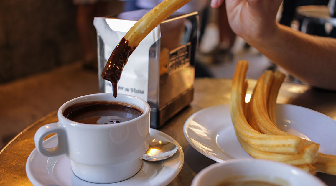 Dipping churro into hot chocolate