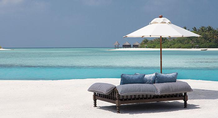 Velvet sofa on the beach with a parasol