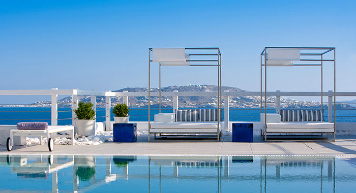 Swimming pool and double cabanas with the sea in the background at Grace Mykonos