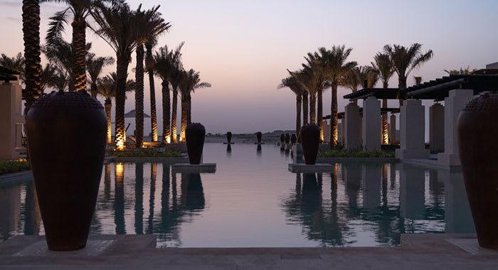 Al Wathba swimming pool and palm trees at night