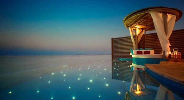 Over water villa infinity pool at night with twinkly lights