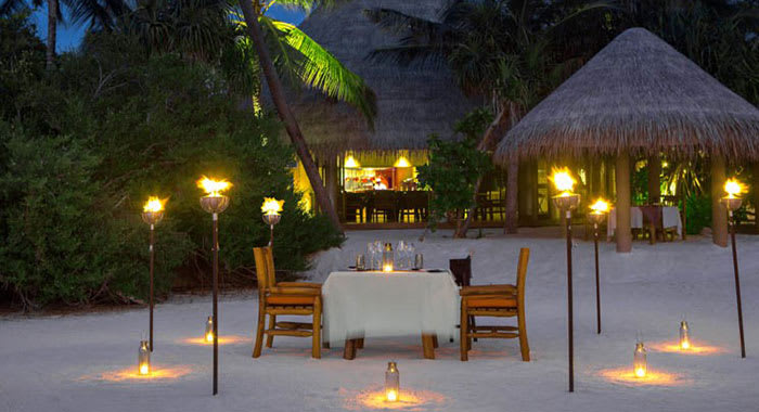 Private dining on the beach surrounded by lanterns