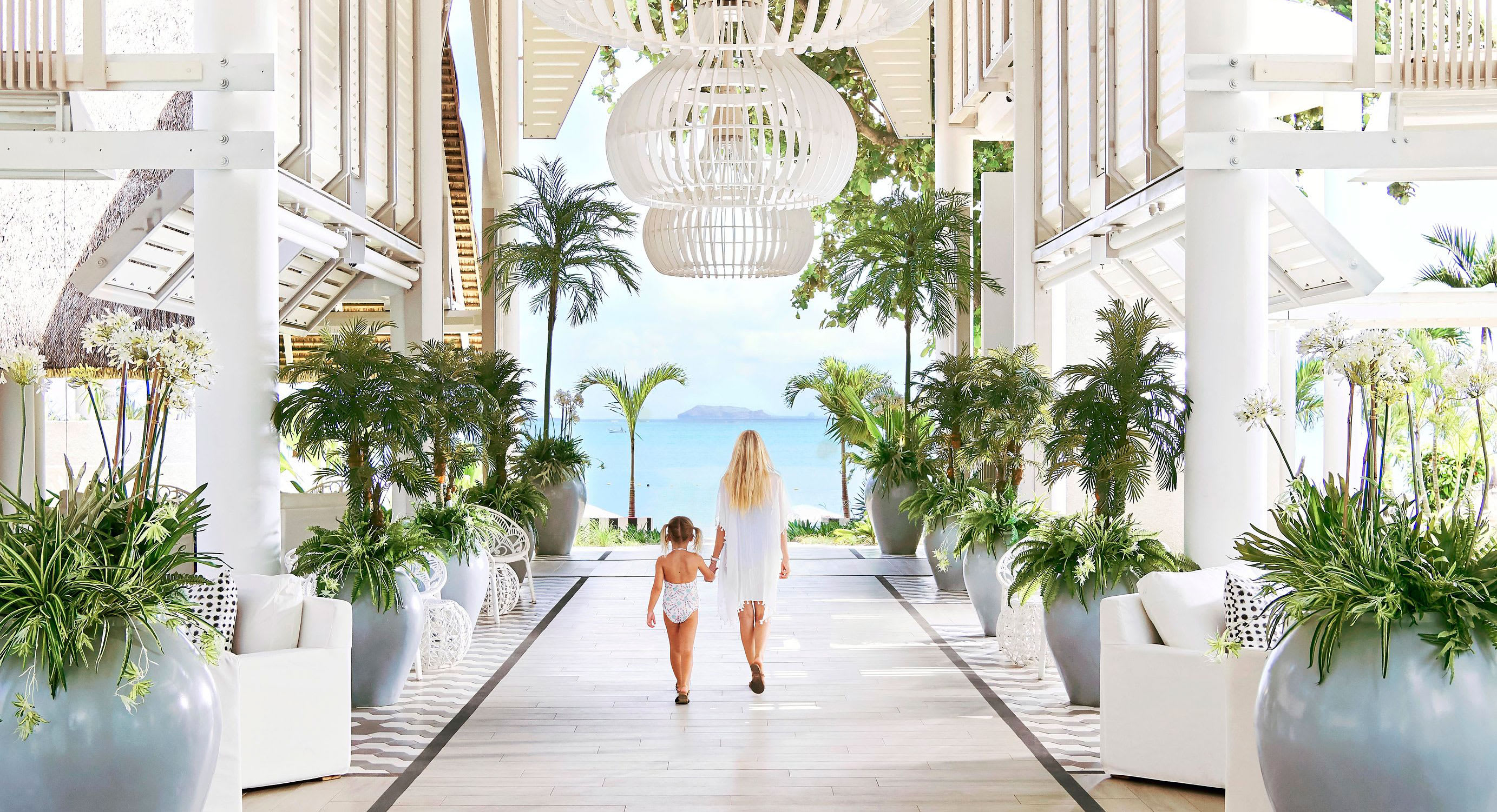 A white lobby with green plants with a view out to the blue ocean