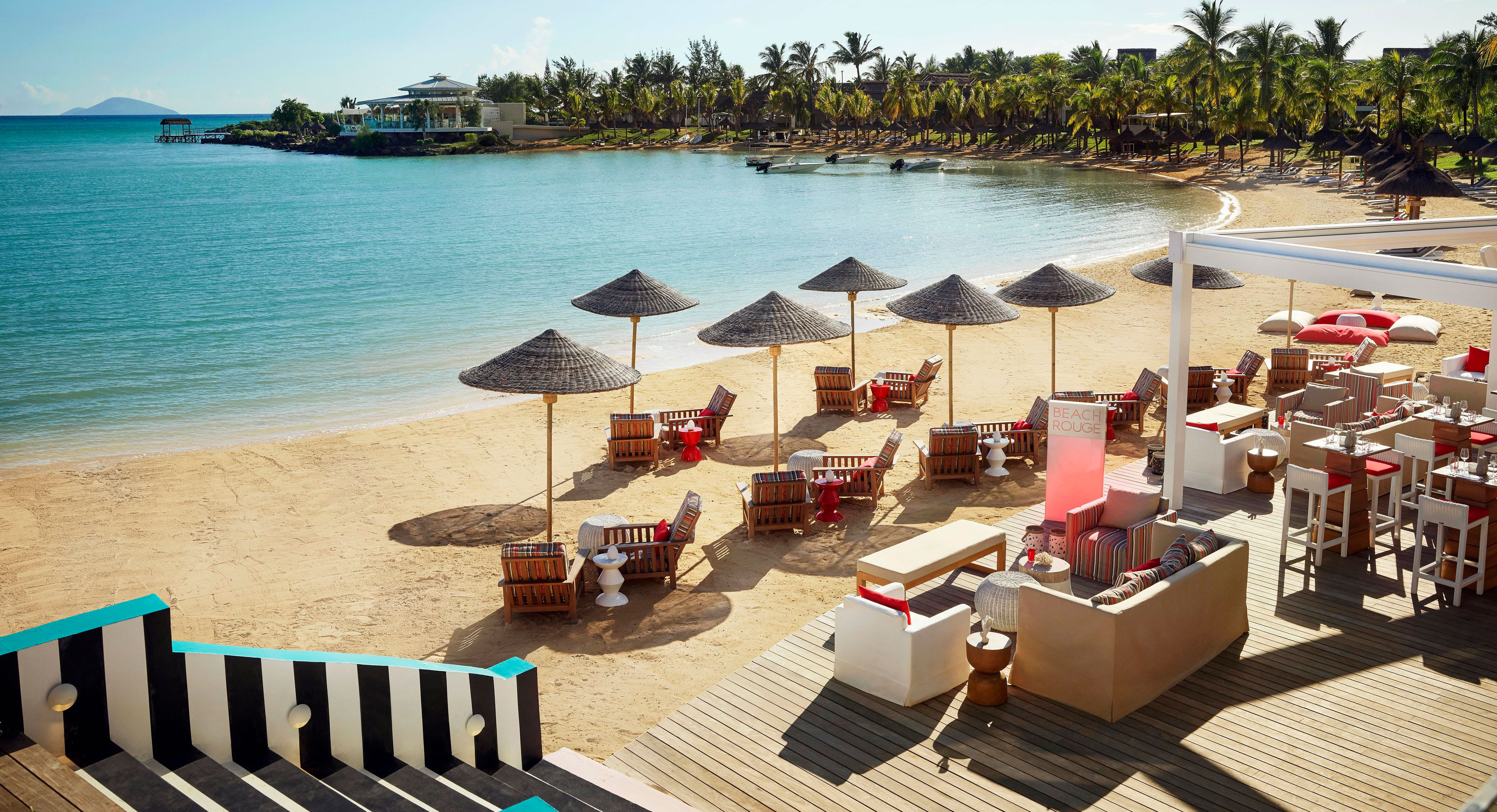 A Mauritian beach with sun loungers, parasols and tables