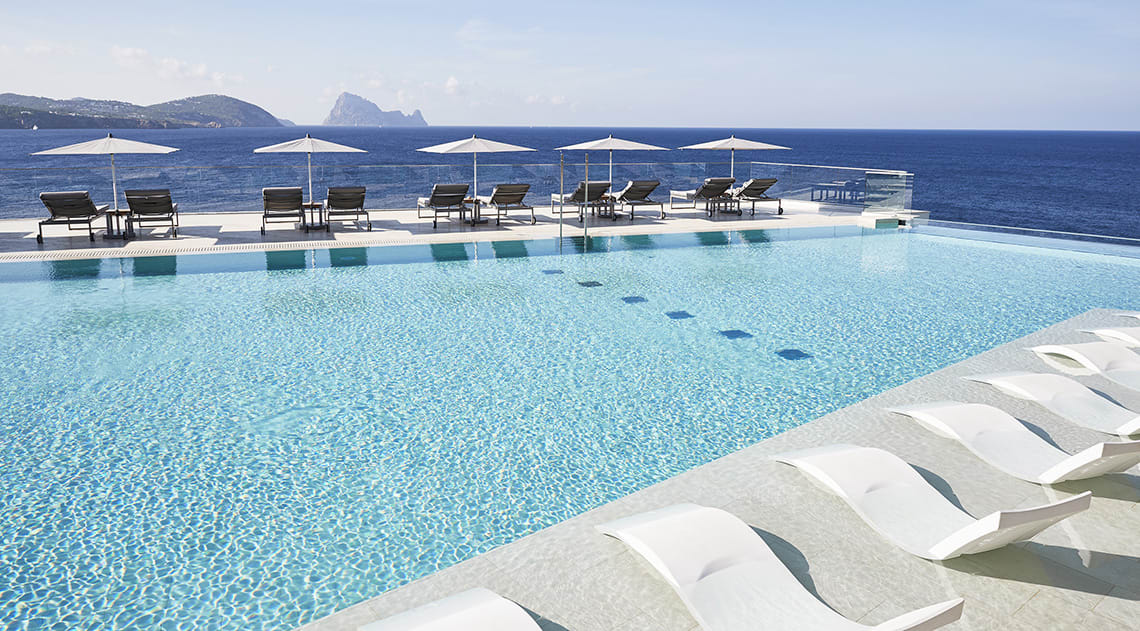 Indinity pool with sunbeds and views of the sea