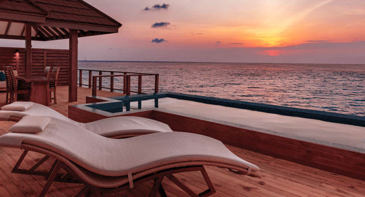 Sunbeds and infinity pool as sun sets over the sea