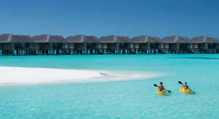 Kayaking couple with over water villas as backdrop