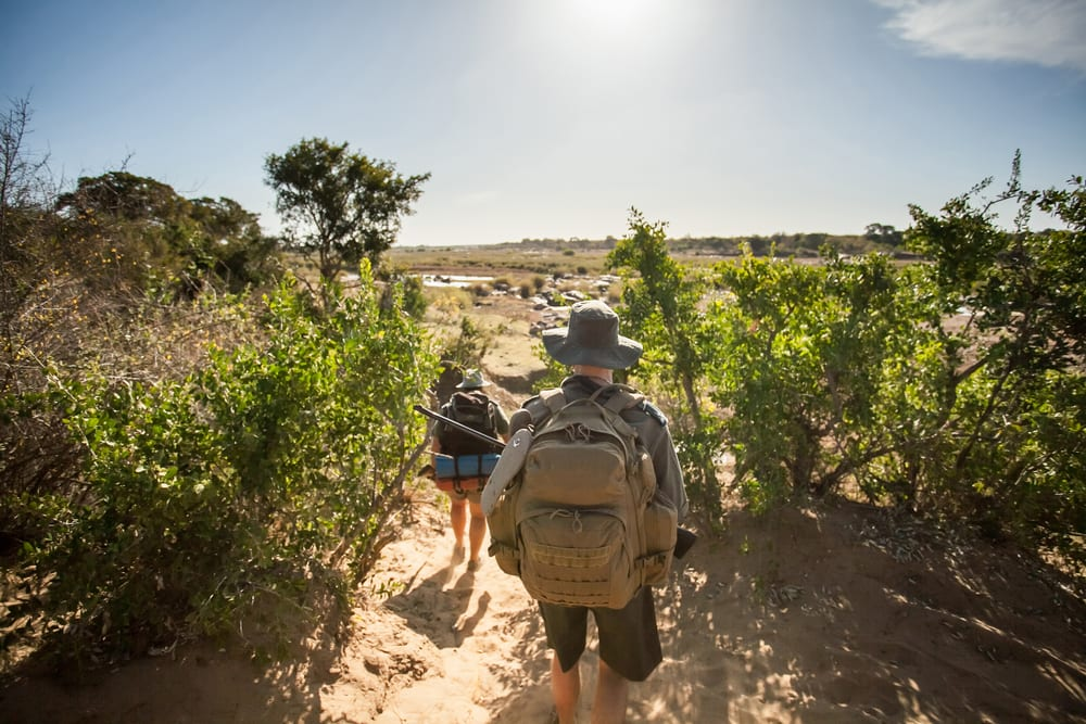 A man and woman walking on sarai with backpacks and camping gear