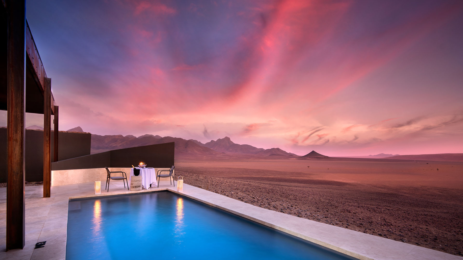 Swimming pool with te desert in the background as the sunsets with a pink sky