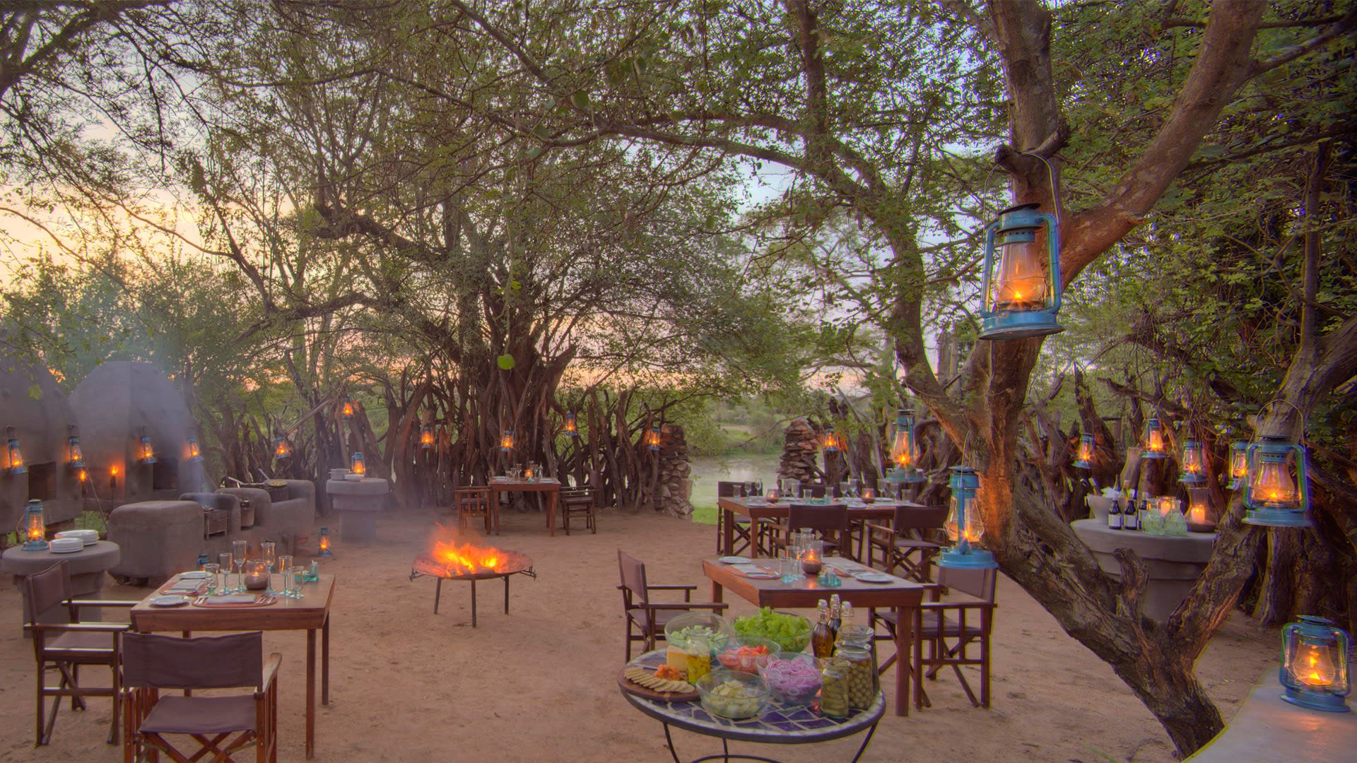 Bush sundowner with lantersn and tables and a firepit