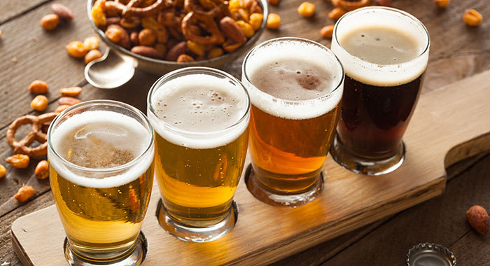 Craft beers lined up on a board with nuts and pretzels in a bowl
