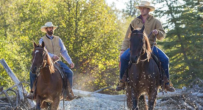 Kananaskis Country two men riding horses through water